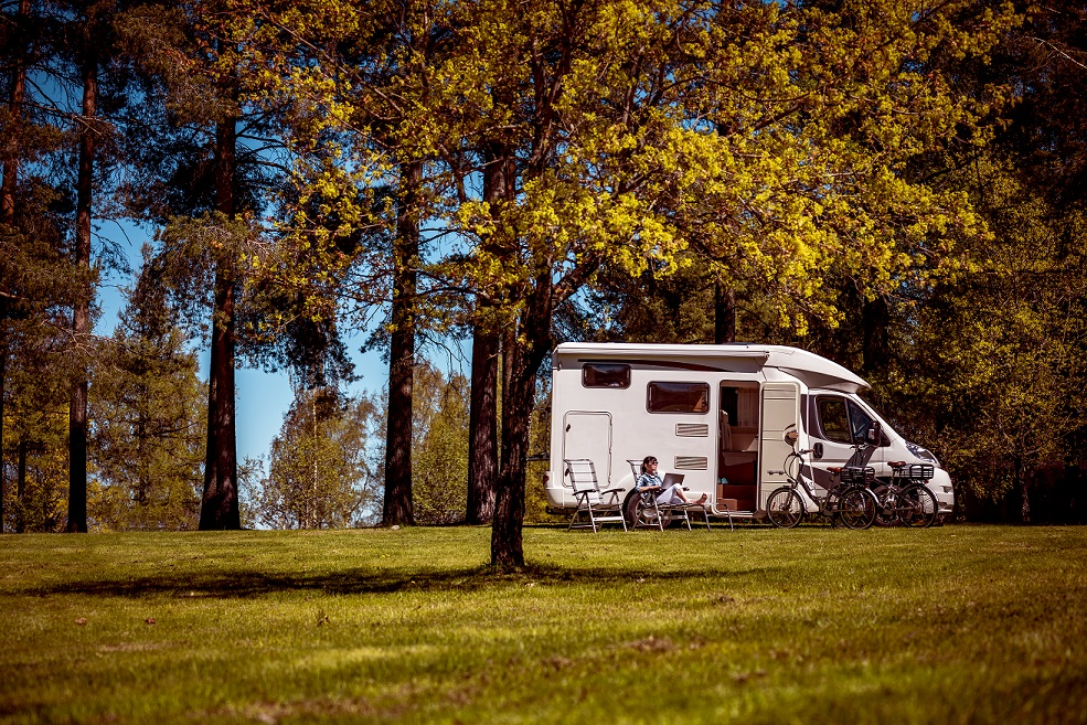 Two people sitting outside of their motorhome on a sunny day