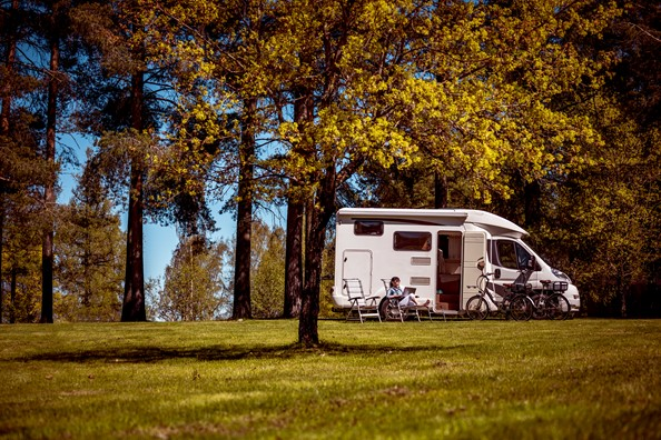 Motorhome set up in field dotted with trees with owners sitting outside