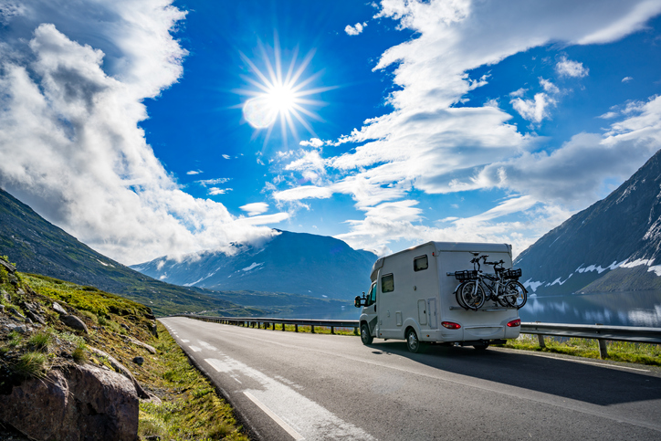 A motorhome with bikes attached to the back driving up a scenic mountain road