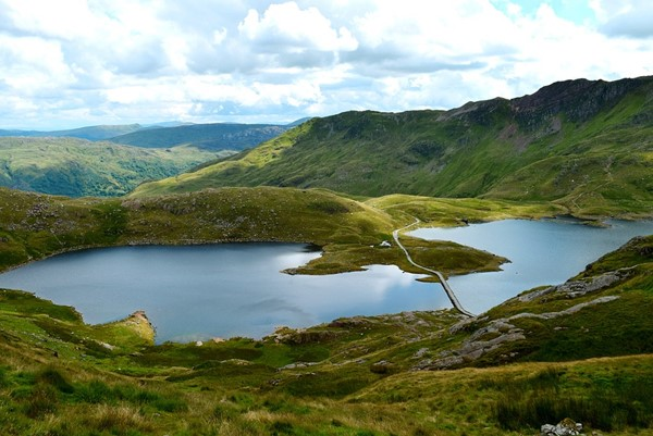 Green mountainous landscape of Snowdonia National Park with blue lake sitting in a valley