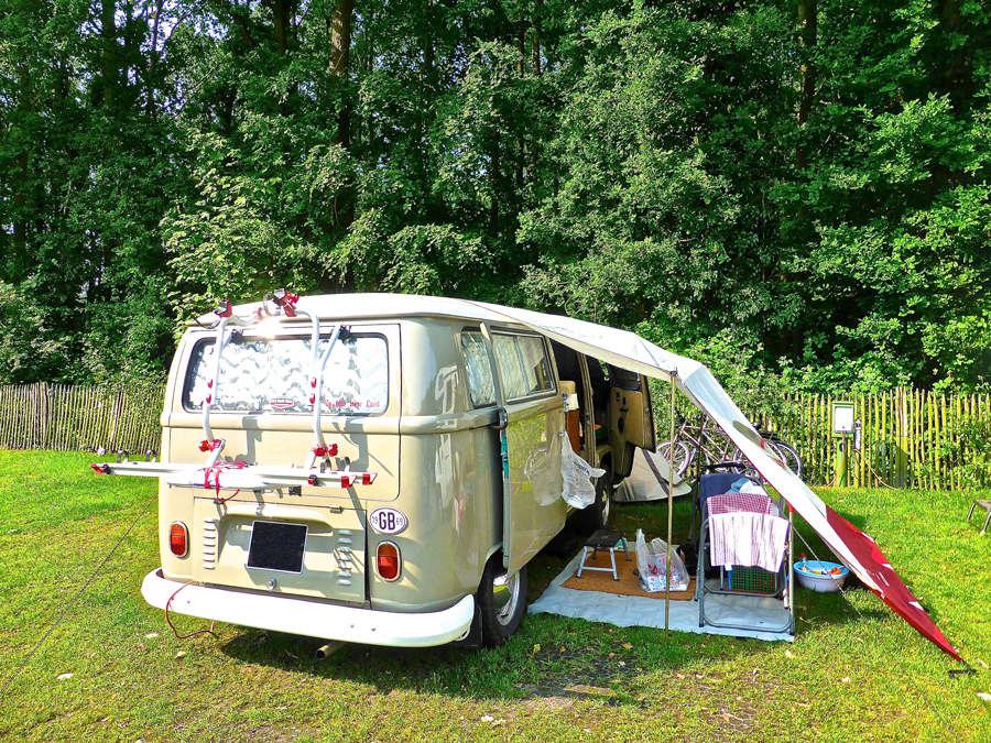 A campervan set-up on a grass pitch at a campsite