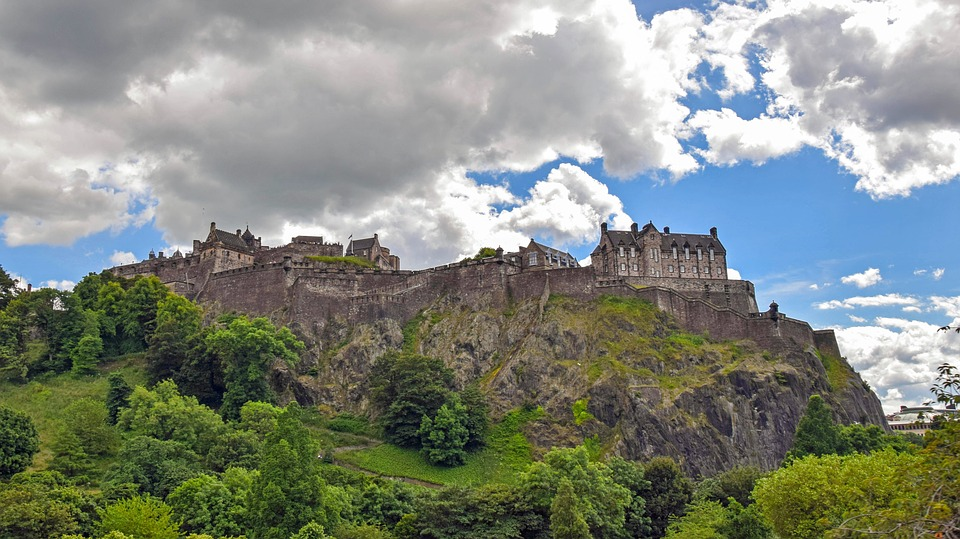 Edinburgh Castle upon a rocky hill surrounded by greenery.