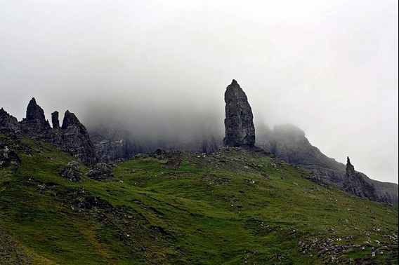 A view of a large sharp rock column shrouded in fog on a green rocky hillside