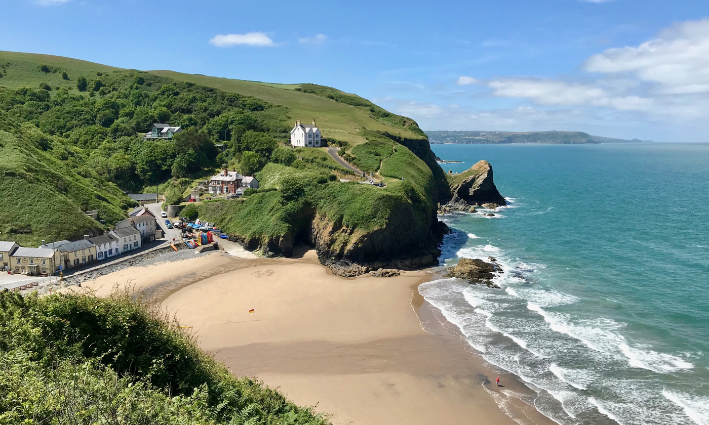 A scenic view over a sandy bay at Ceredigion, surrounded by grassy cliffs with a small village looking out to the blue sea