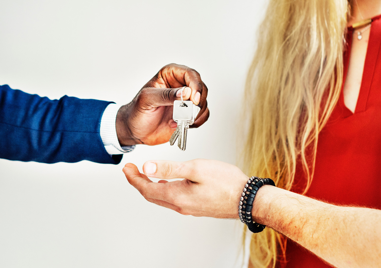 A salesman handing over the keys to a vehicle to a customer