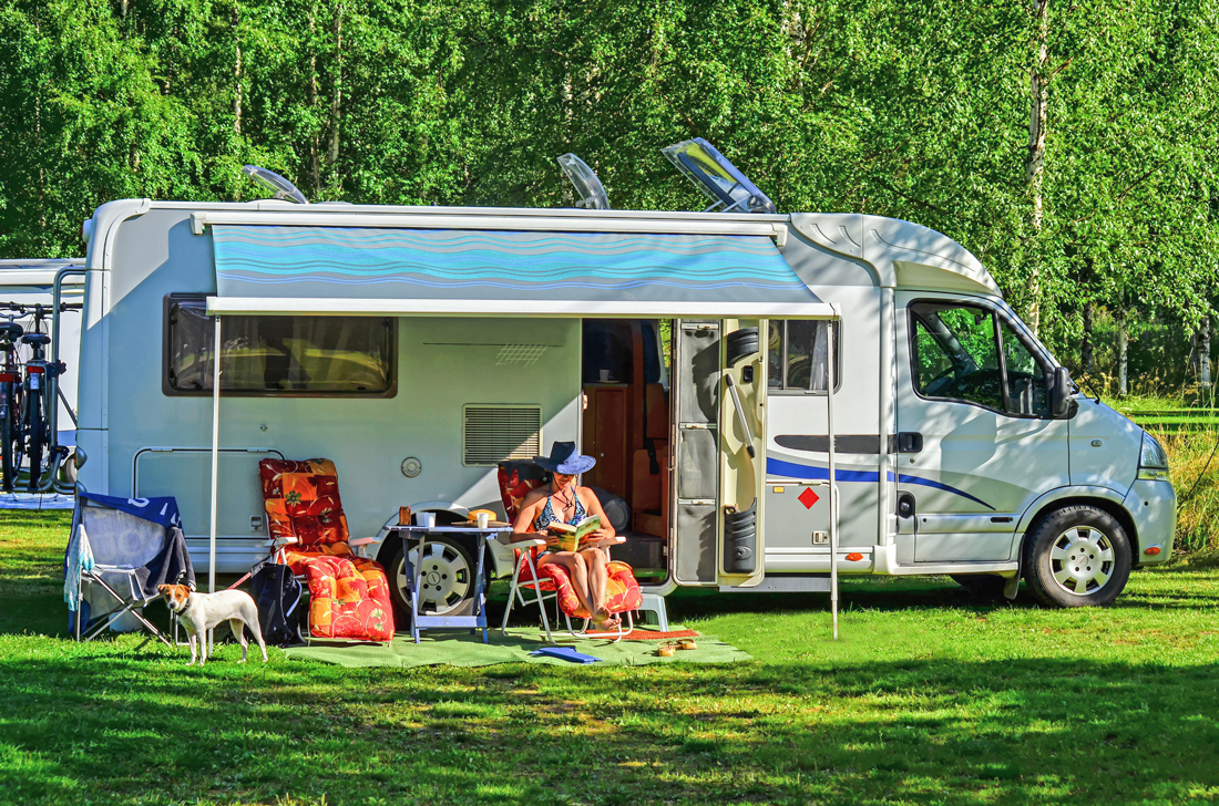Class-A motorhome set upon a campsite with canopy and chairs outside