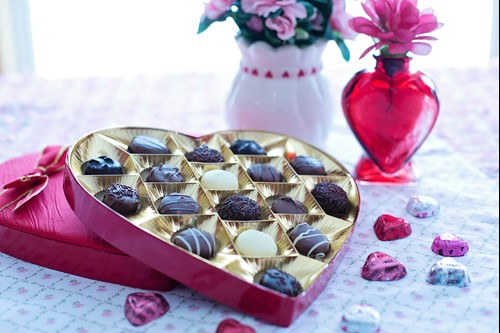 A heart shaped box of chocolates on a table next to some flowers