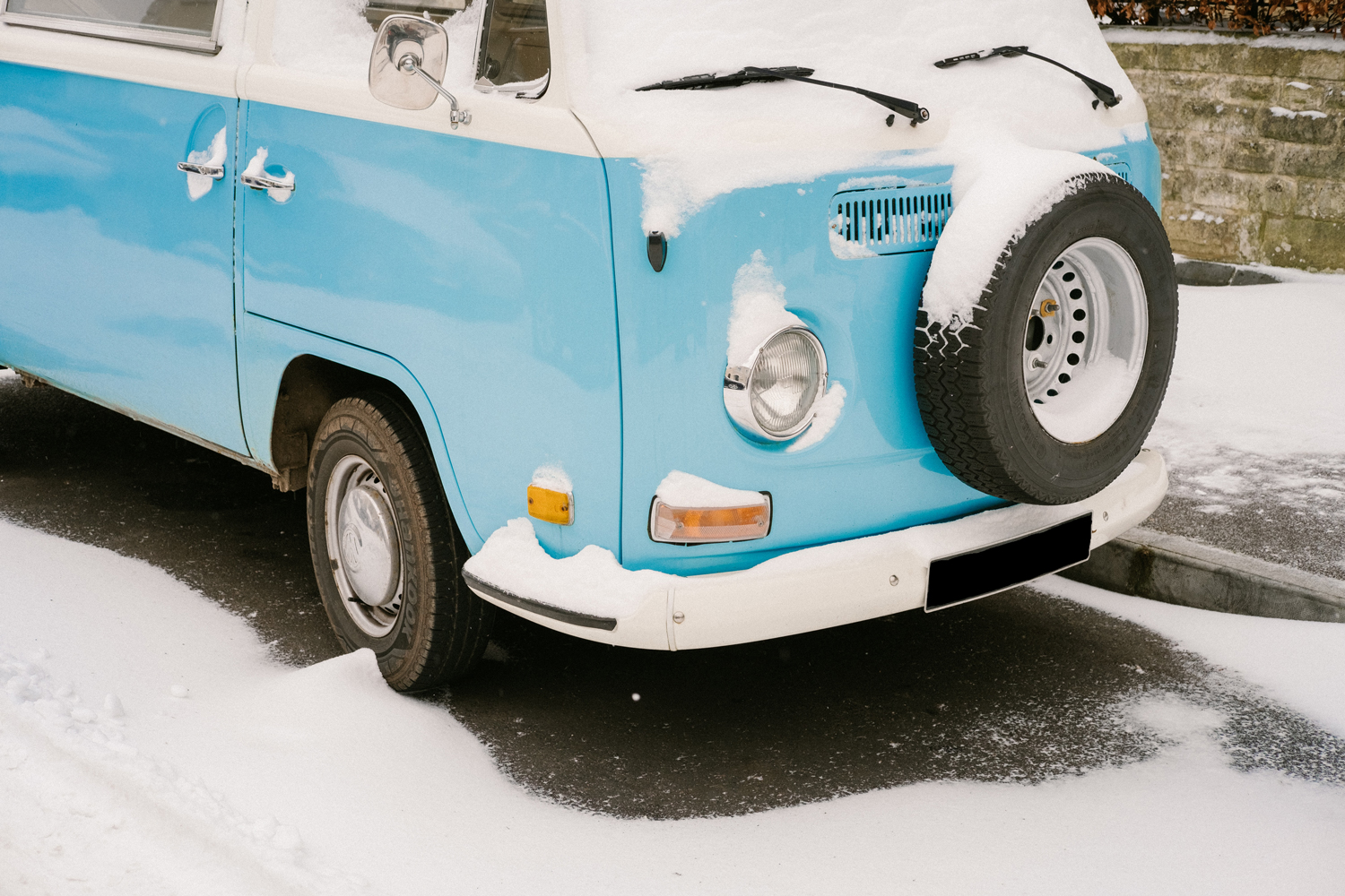 A vintage campervan parked at the side of a road covered in snow