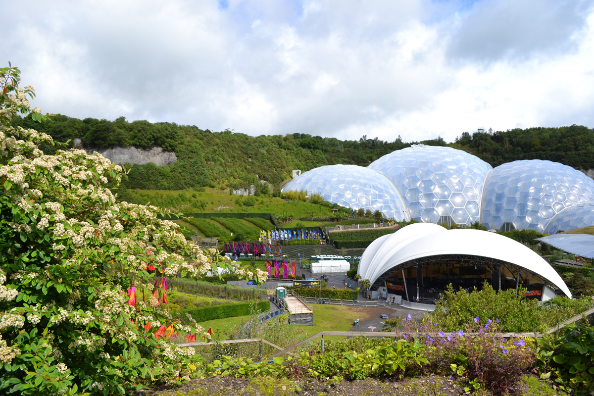 A green hill side with large transparent domes and a visitor centre