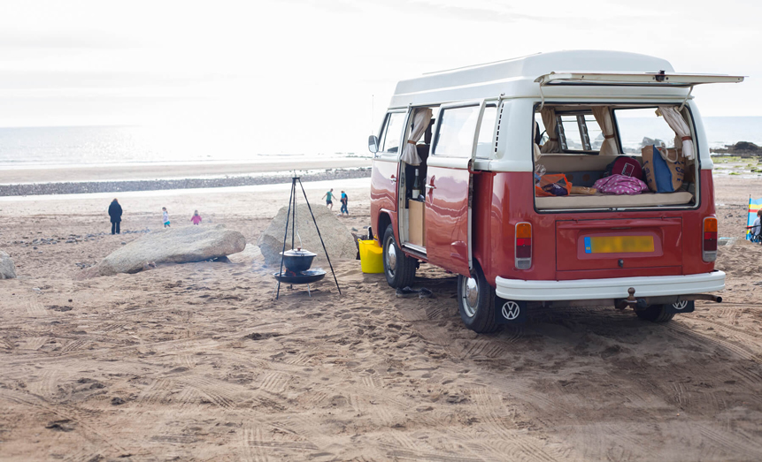 red campervan on beach sea front