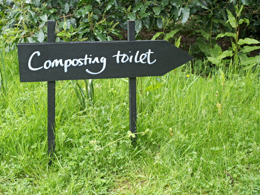 A sign pointing to a composting toilet on a campsite