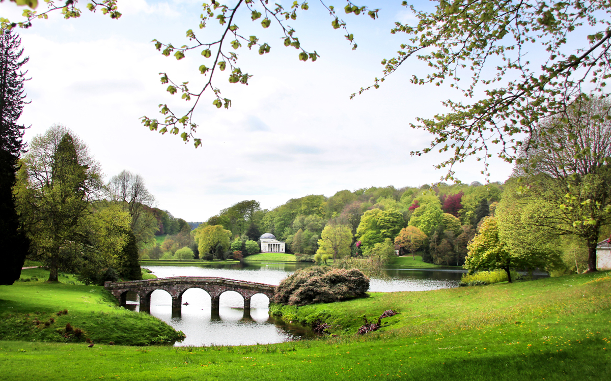 A stone bridge over a lake surrounded by forest and green grass