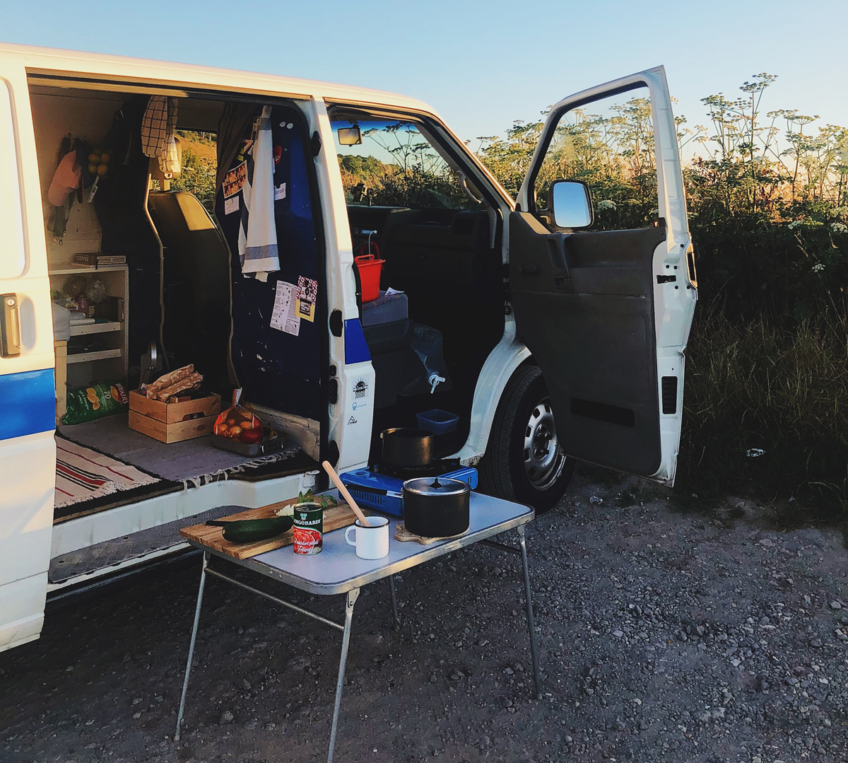 A campervan set up next to a crop field with a table set up outside for cooking