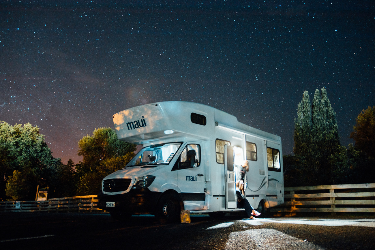 A motorhome pitched on a gravel campsite on a starry night