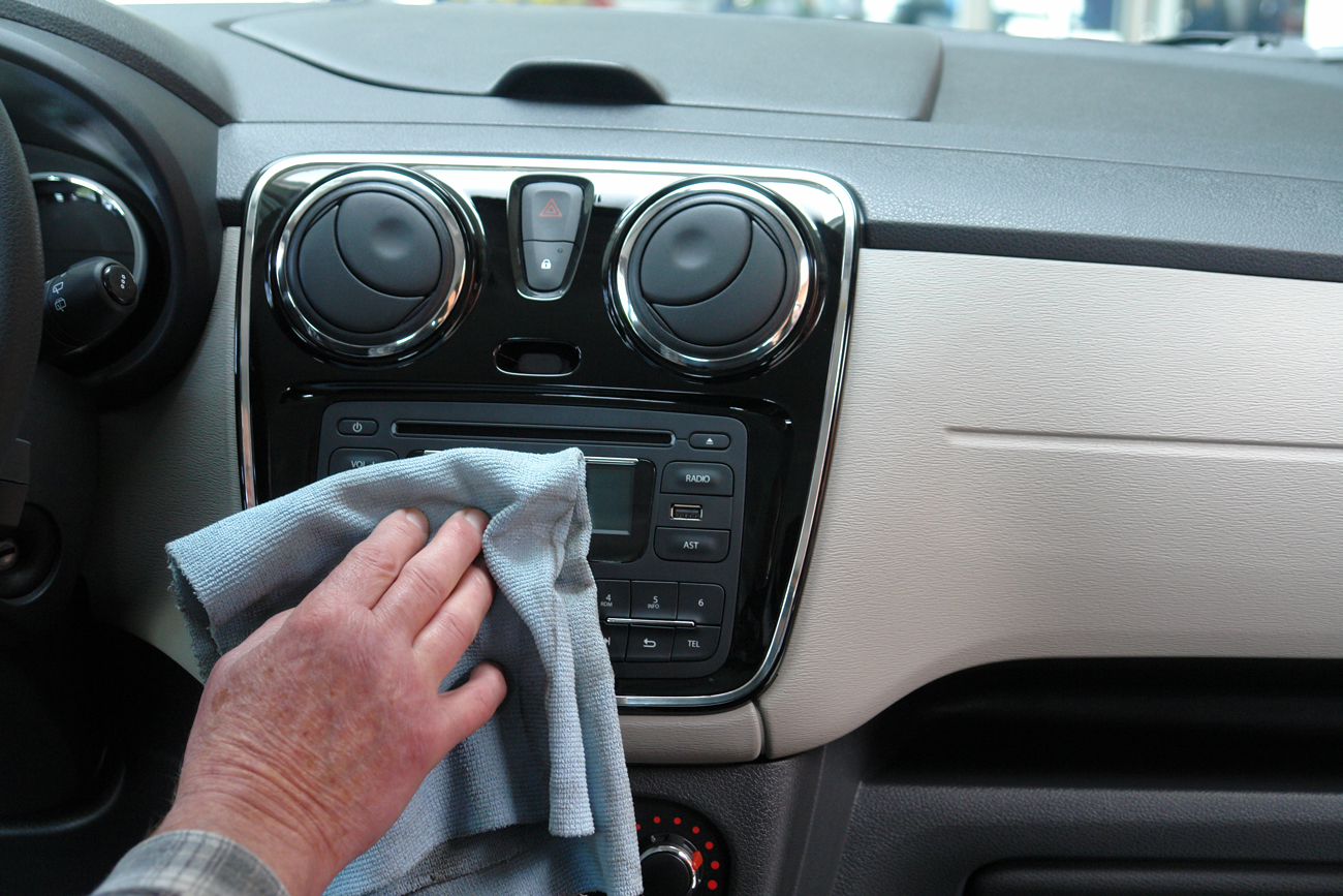 A person using a cloth to clean the dashboard of their motohome