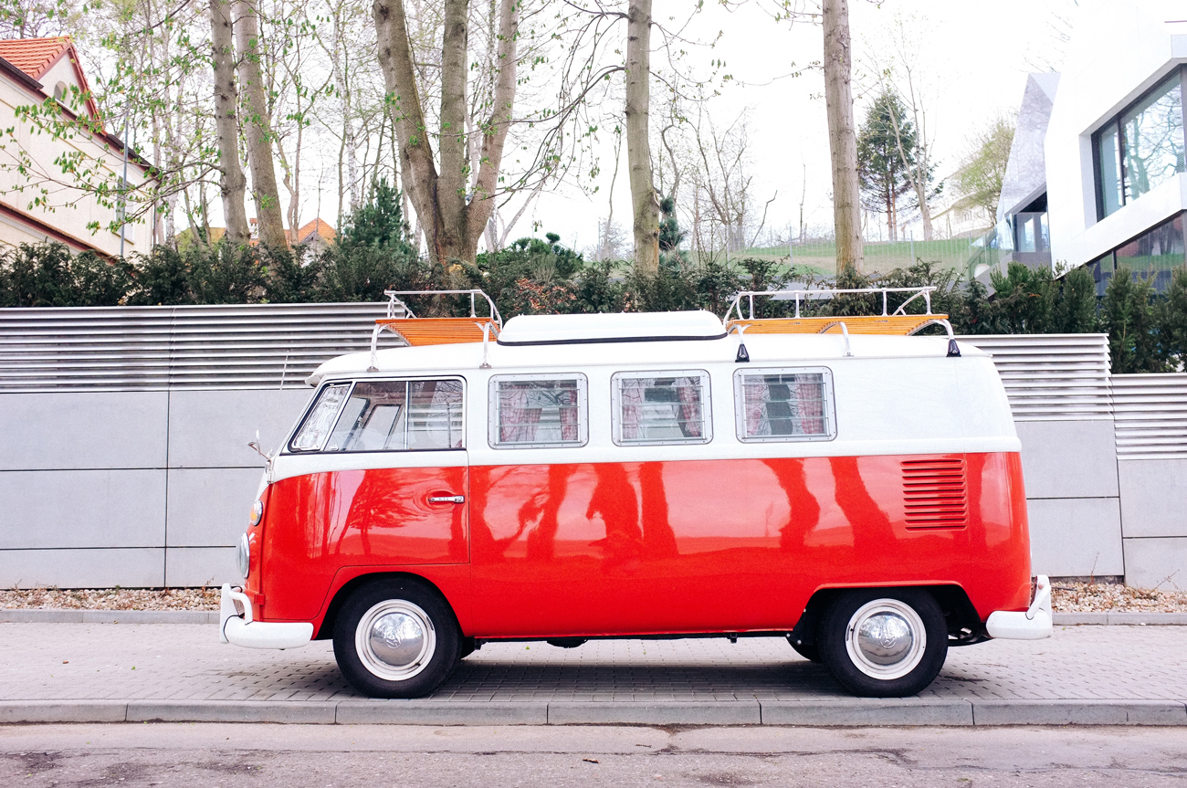 A classic red campervan parked on a pavement in a residential area on a cloudy day
