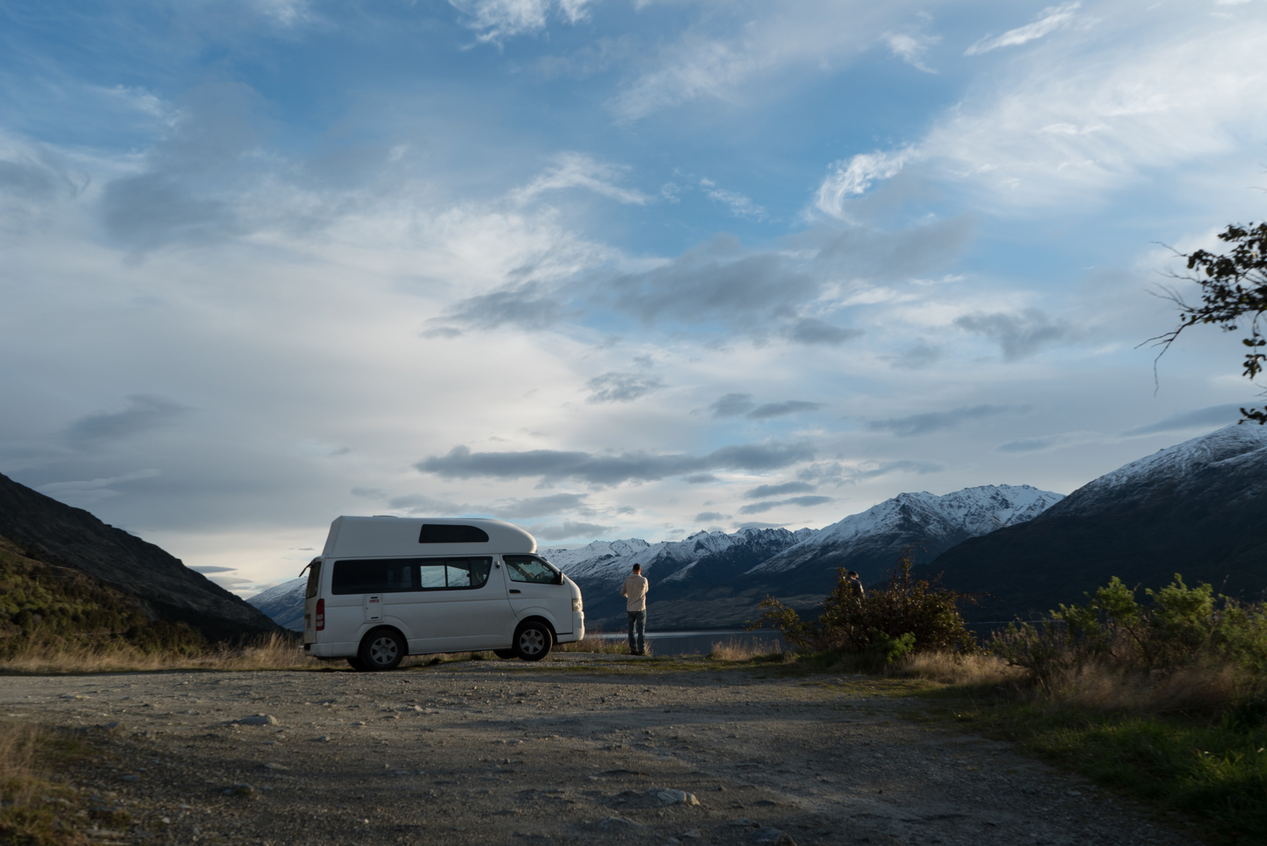 A single campervan parked in the middle of an open gravel area with mountains in the distance