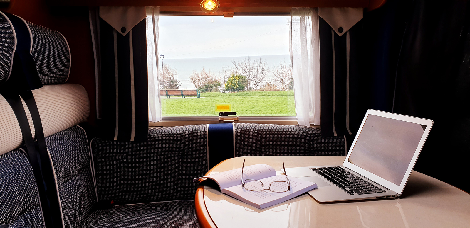 The interior of a motorhome with a laptop and notepad set-up on the table