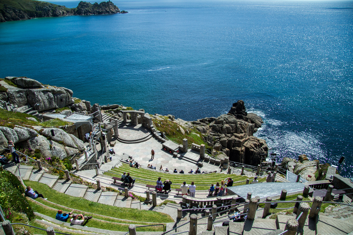 A steep stone theatre on a rocky cliff looking over the blue Cornish sea on a sunny day