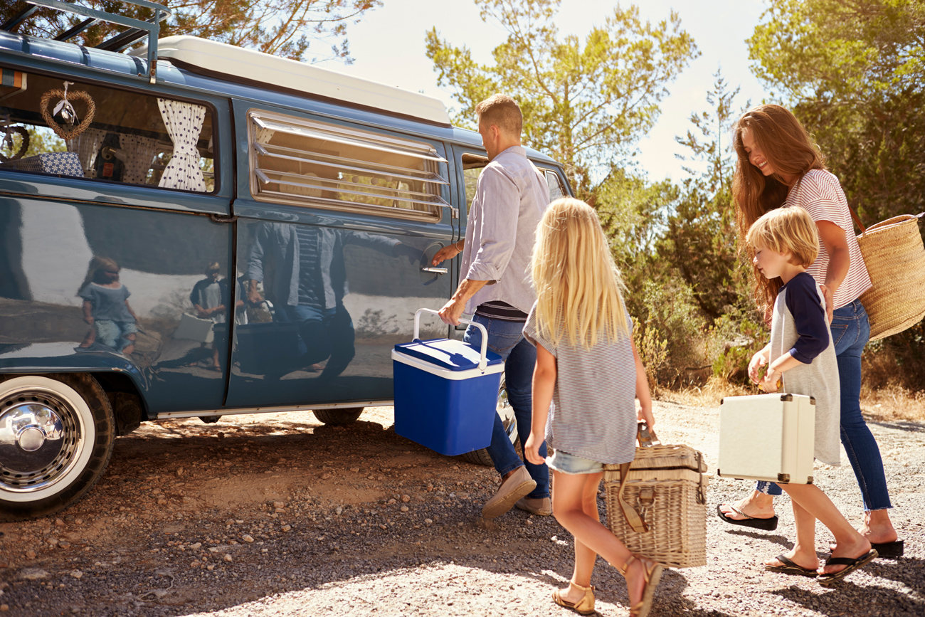A family walking over to a campervan with picnic bags