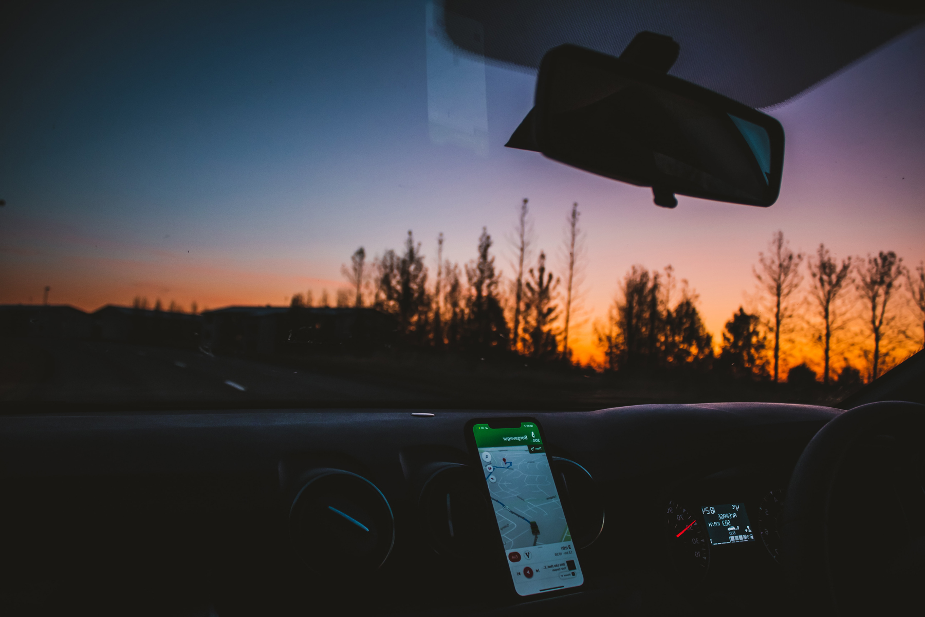 The interior of a car with the driving using Google maps for navigation at sunset