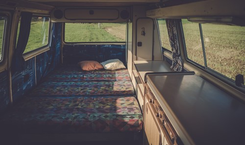 A campervan interior with a colourful bed