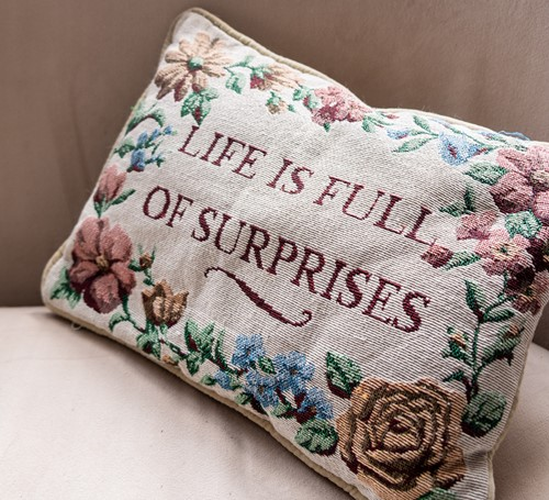 A cushion wit a quote on it on a sofa in a campervan