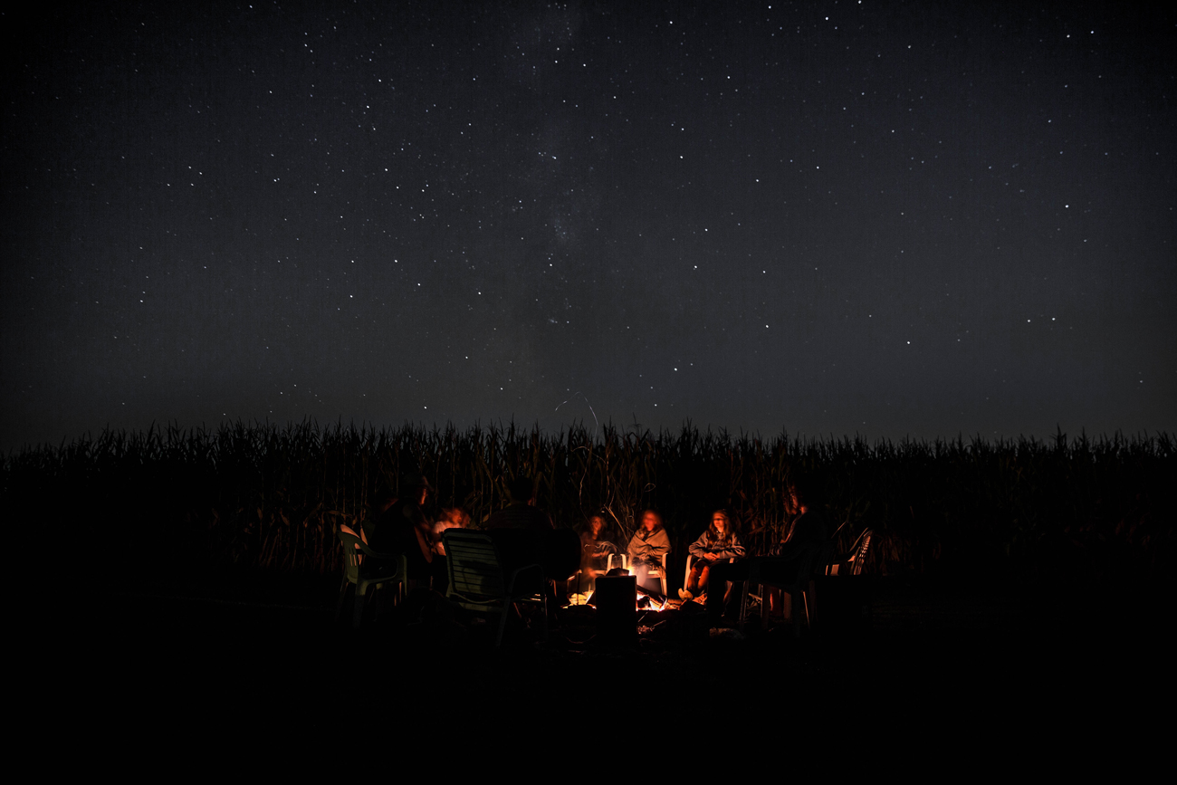A family sat around a campfire at night