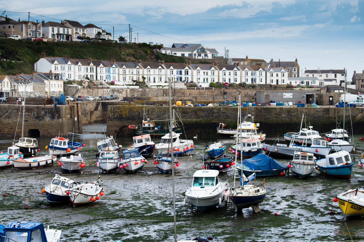 The town of Porthleven on the Cornish coast with many small fishing boats anchored in the harbour