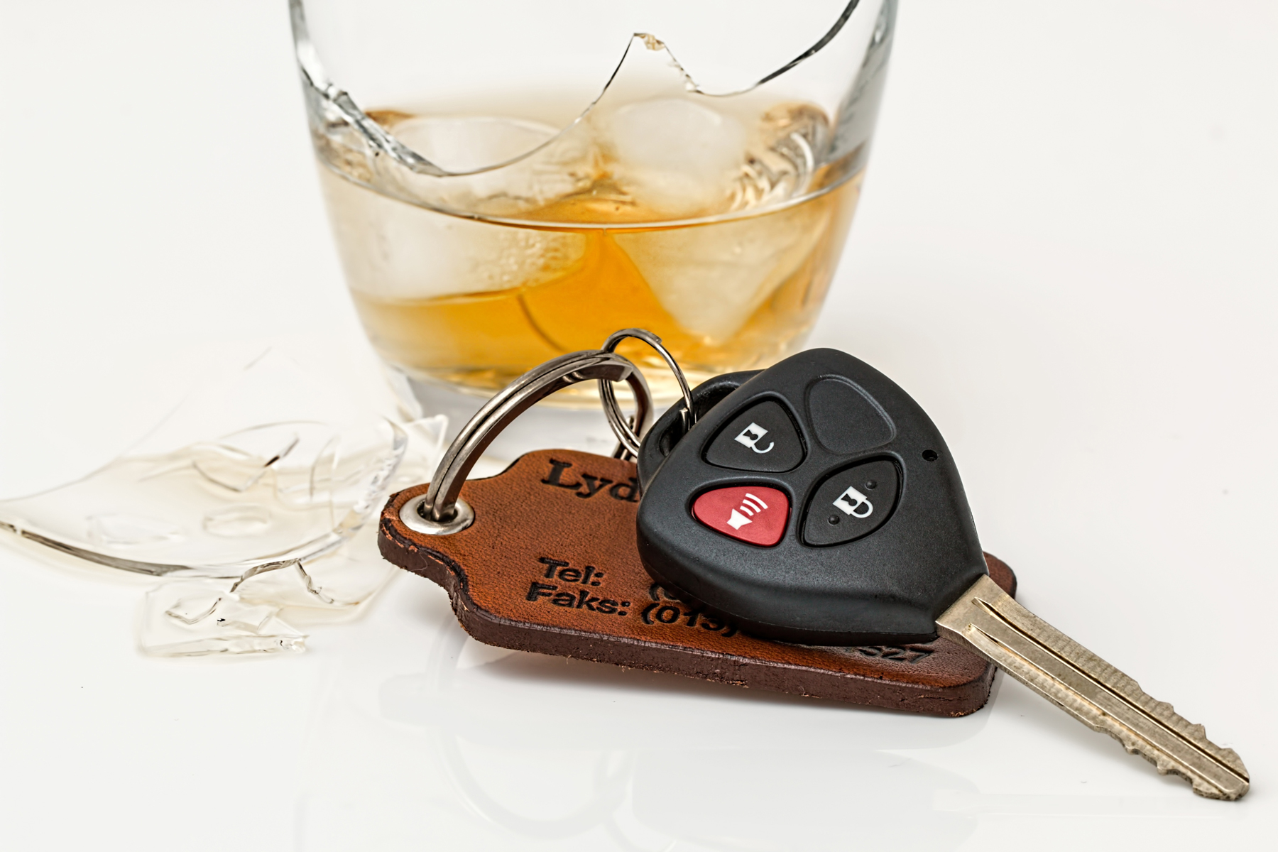 A pair of car keys on a table with a broken glass containing alcohol behind