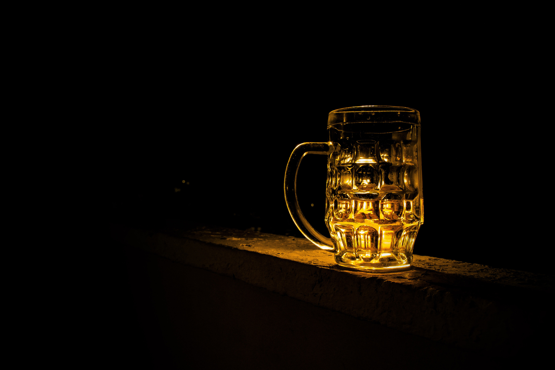 A beer glass on a table in a dark room