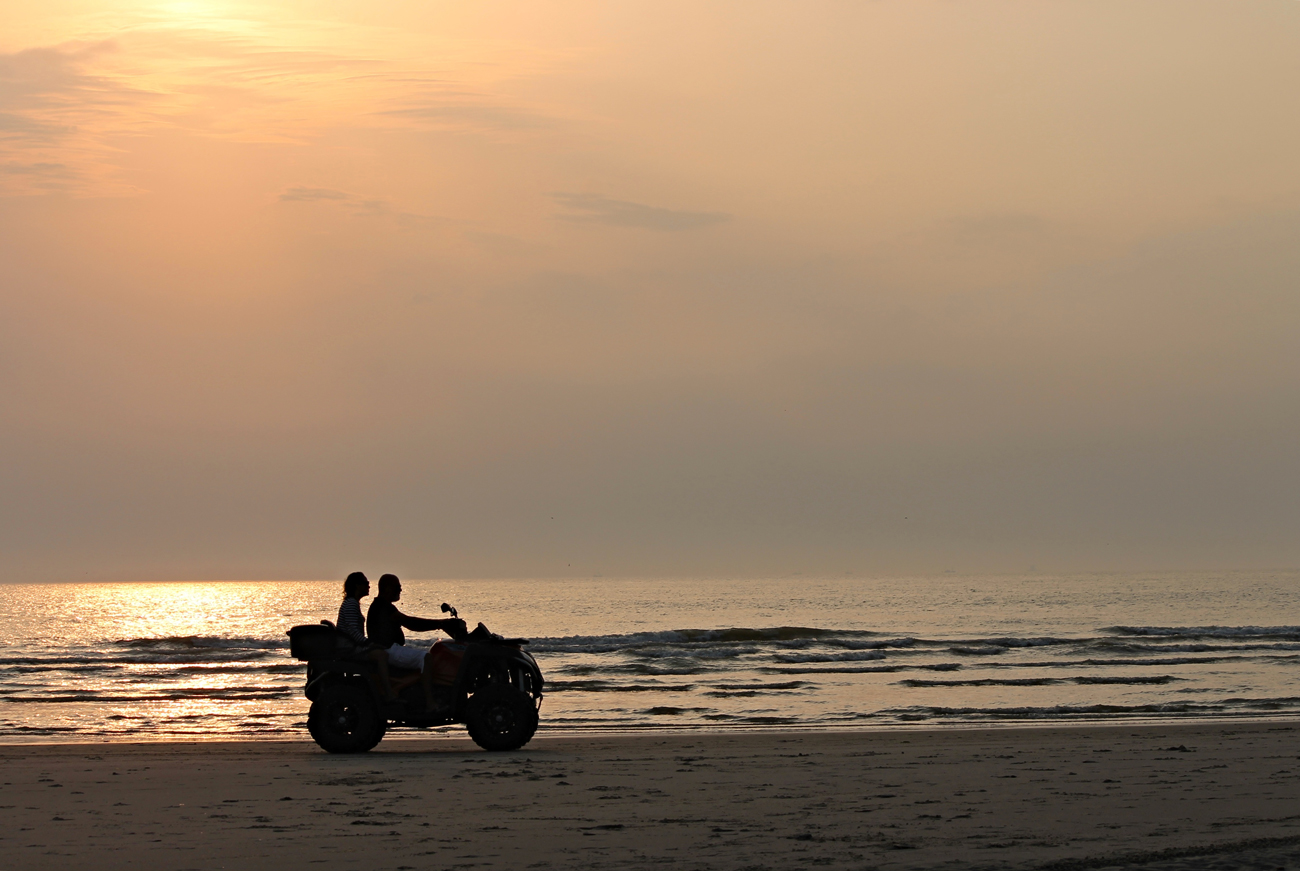 A quadbike driving along a sandy beach at sunset