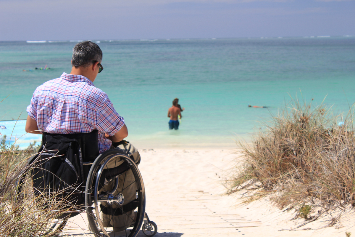 A man in a wheelchair sitting on a sandy beach looking out to sea on a sunny day