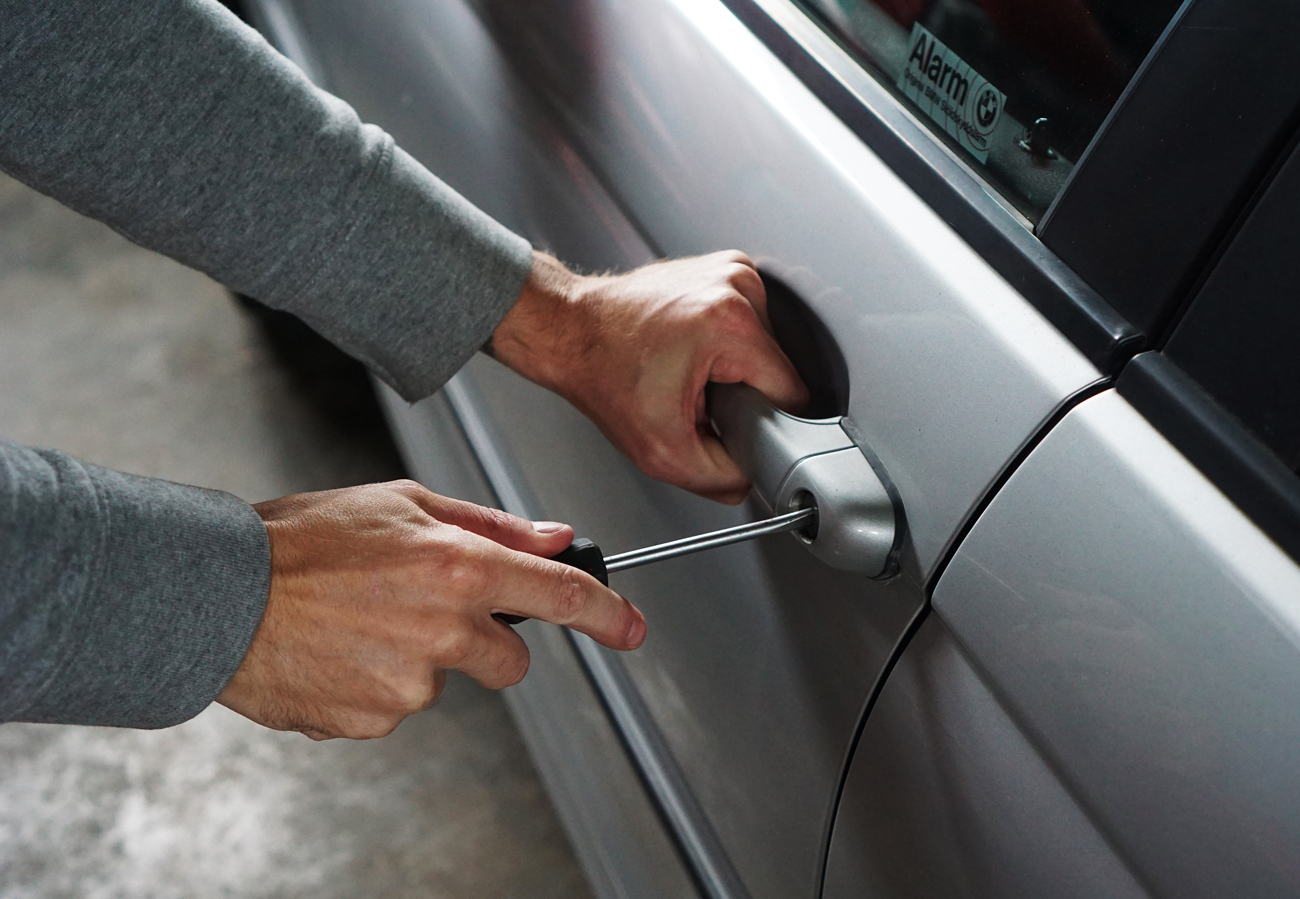A man using a screw driver to break into a vehicle