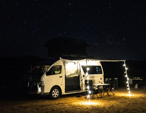 A campervan set-up under a starry night sky with fairy lights attached to its awning
