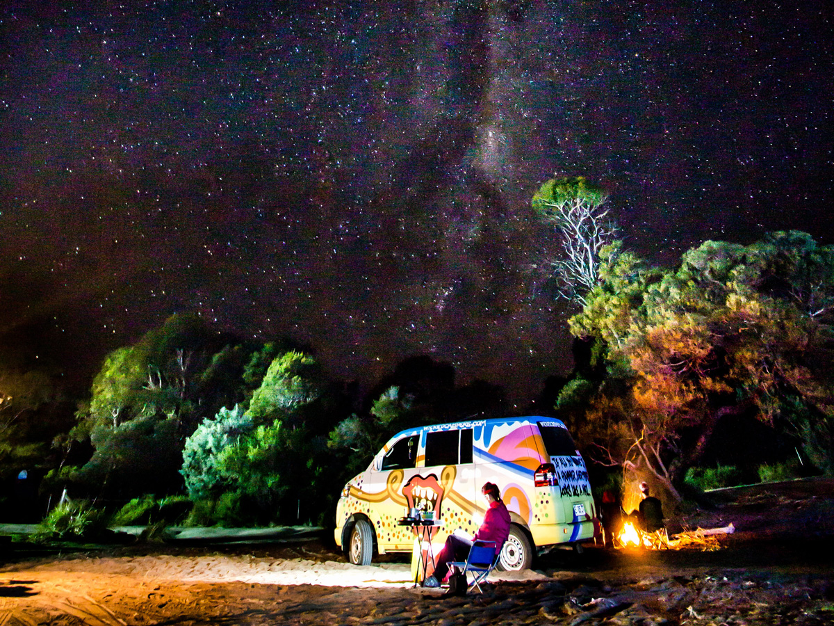 A man sitting in a chair next to a campervan starring up at the stars in the night sky