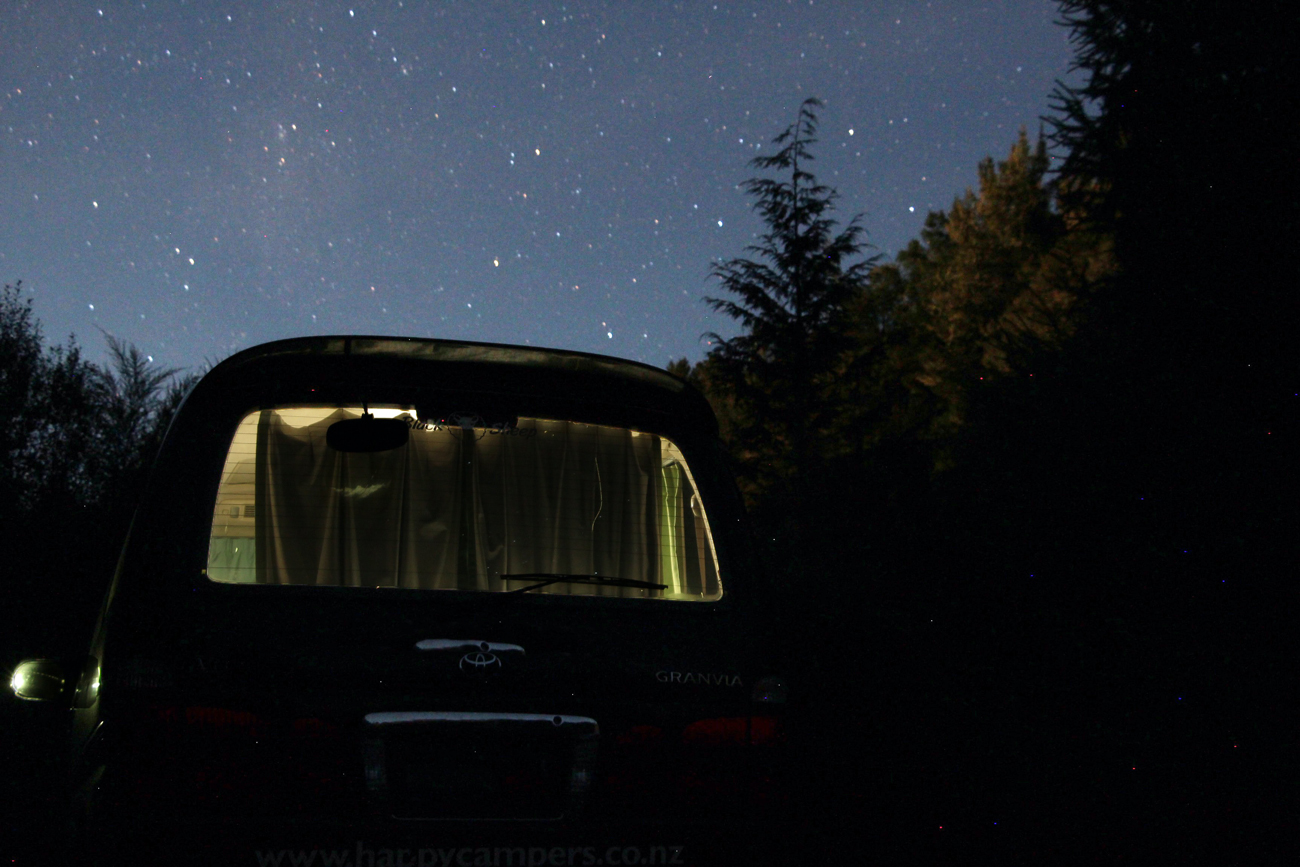 A campervan parked in a wooded area under a starry sky