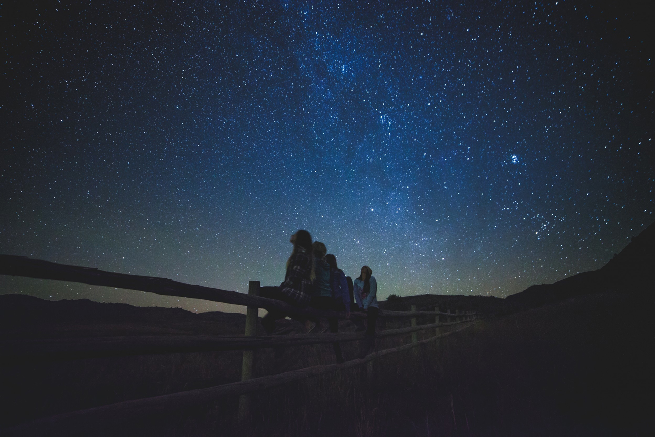A group of friends sitting on a fence in the country side starring up at a star filled sky
