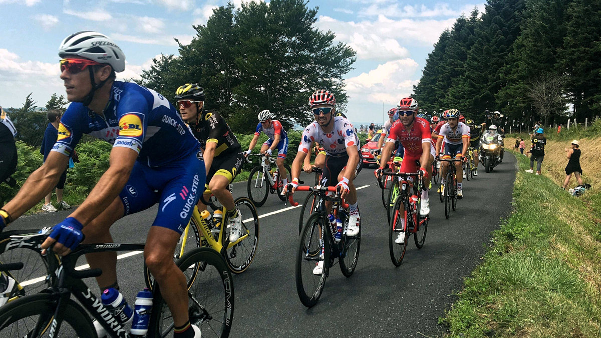 A group of cyclist riding on a country road during the Tour De France