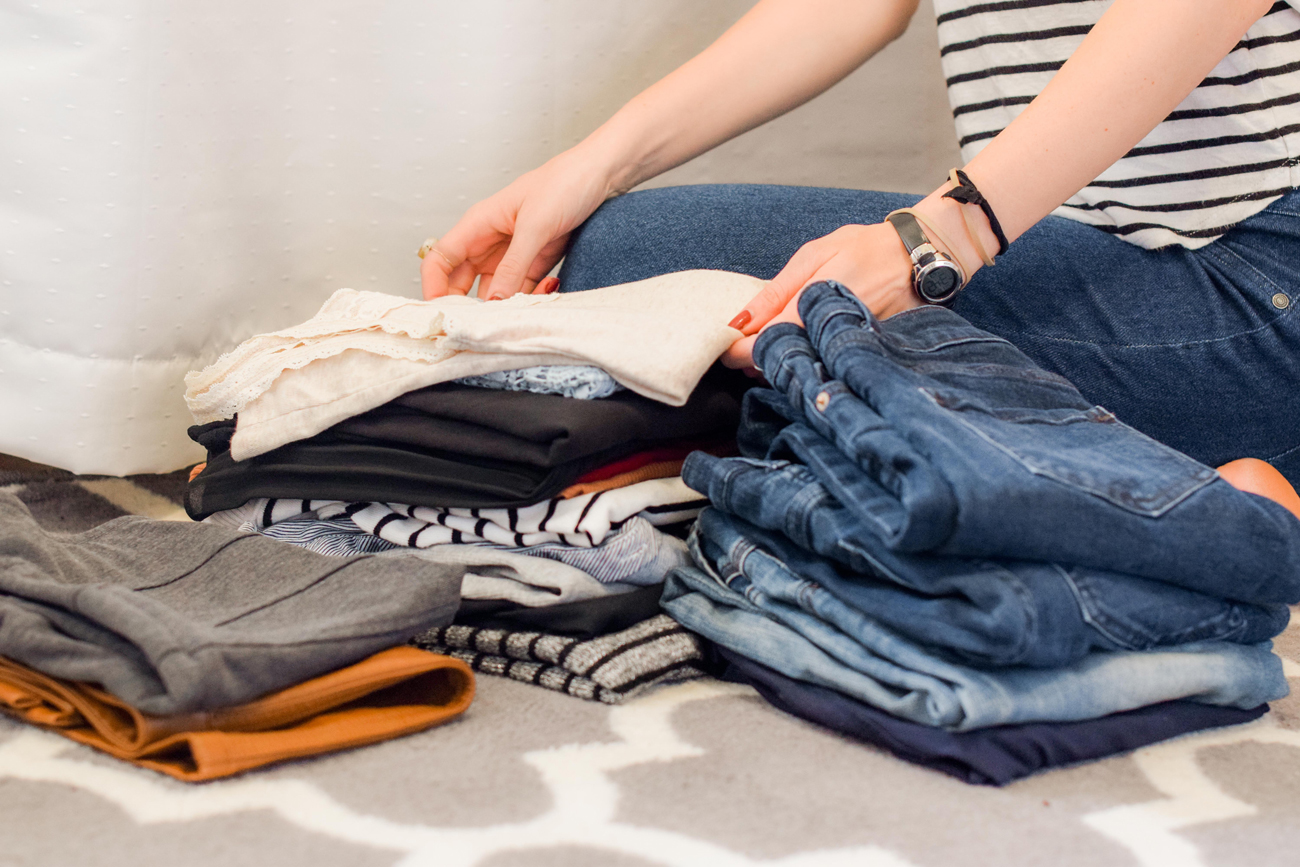 A person folding clothes on a bed