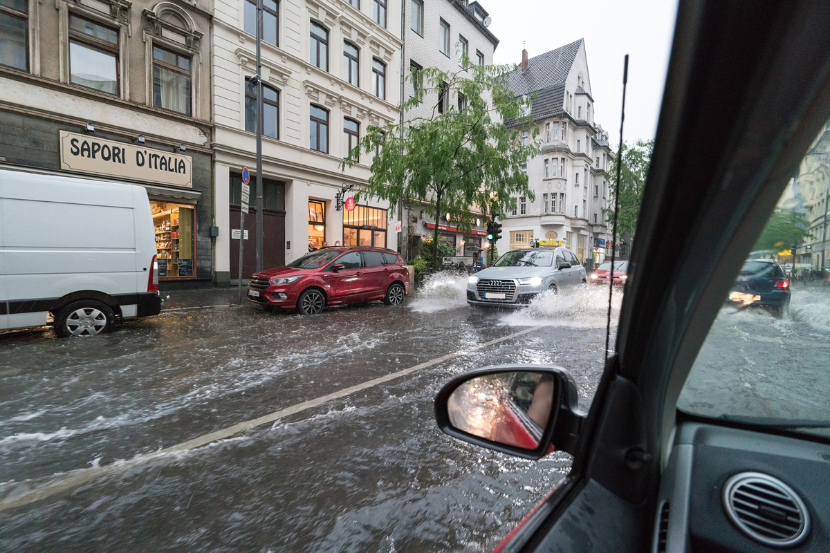 A flooded street in a city with cars driving on either side