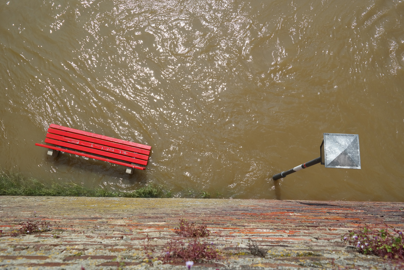 A bench and lamp post viewed from over head on a flooded street