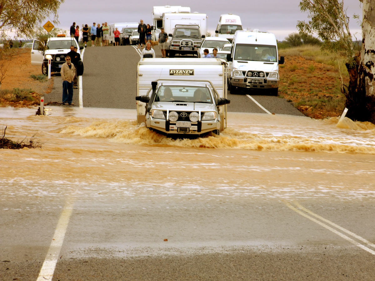 A truck towing a caravan crossing a flooded road with motorhomes behind waiting to cross