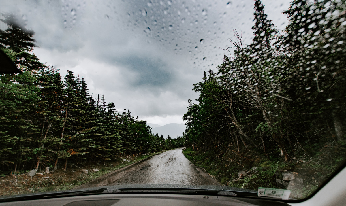 A campervan driving up a country road in a mountainous area in stormy weather
